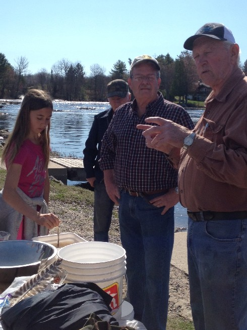 Hatchery member John Hetherington explains to the students the process at the dock with the male and female pickerel ( Brave man)