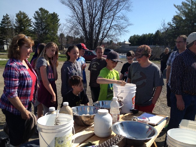 students at the dock helping stir the fertilized eggs before being transferred to the hatchery containers
