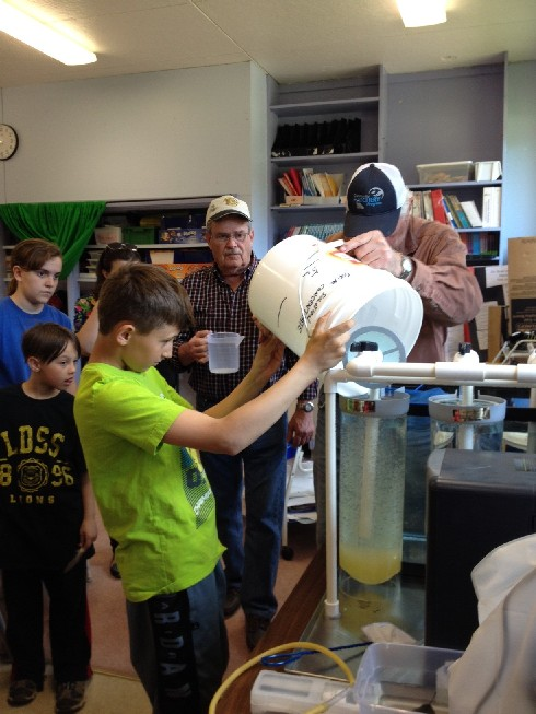 students assist hatchery members to fill the hatchery container with fertilizes eggs at the school hatchery